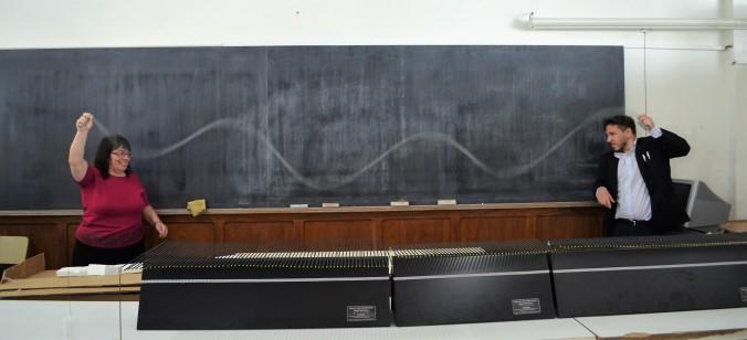 Foto 1. Los profesores Myrian Tebaldi y Damián Gulich muestran el concepto de ondas estacionarias.